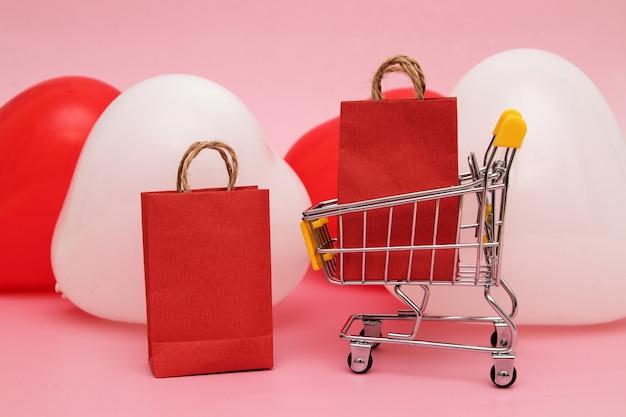 Supermarktwagen mit einkäufen vor dem hintergrund herzförmiger luftballons - verkauf zum valentinstagskonzept