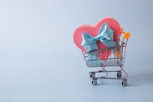 Supermarktwagen mit herzförmigem geschenkbox-valentinstag-verkaufskonzept