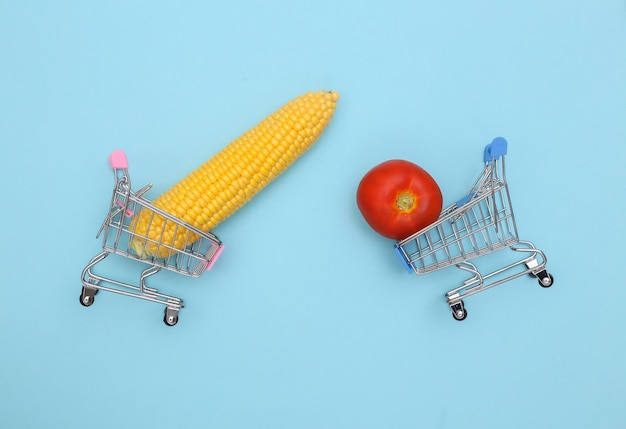Supermarktwagen mit mais- und tomatenschwingen auf blauem hintergrund.