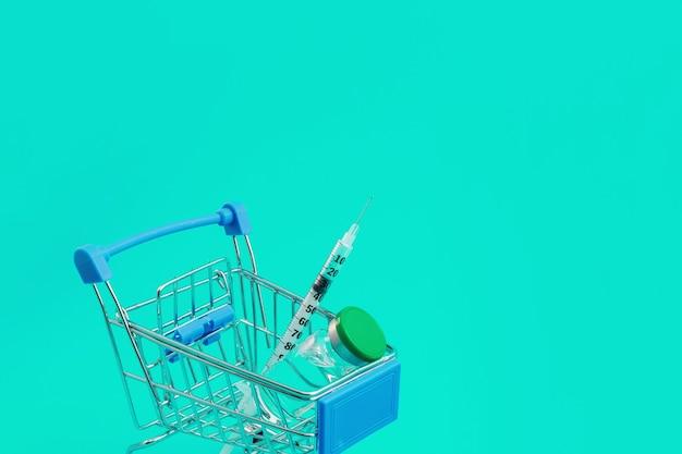 Supermarktwagen mit spritzen und ampulle auf blauem hintergrund