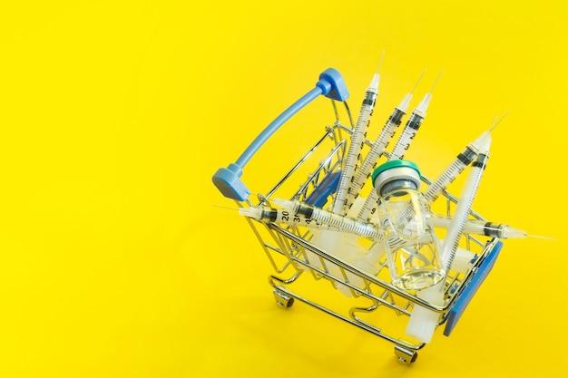 Supermarktwagen mit spritzen und ampulle auf gelbem hintergrund