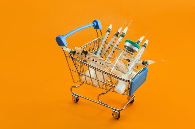 Supermarktwagen mit spritzen und ampulle auf orangem hintergrund