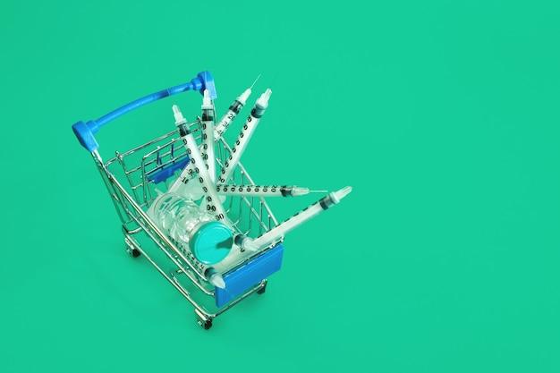 Supermarktwagen mit spritzen und ampulle isoliert
