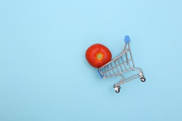 Supermarktwagen mit tomate auf blauem hintergrund.