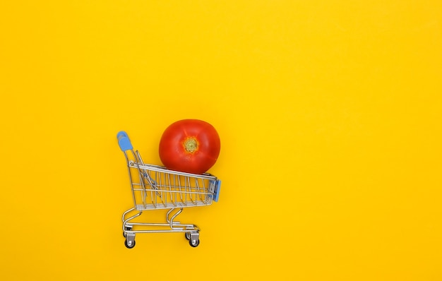 Supermarktwagen mit tomate auf gelbem hintergrund.