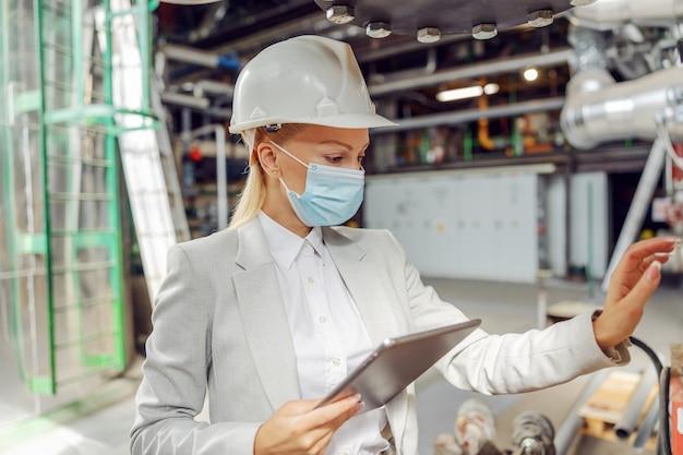 Supervisor mit gesichtsmaske im heizwerk neben dem armaturenbrett, einstellungen anpassen.