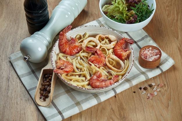 Suppe auf der brühe mit nudeln und garnelen, tintenfisch in weißer keramikschale auf holztisch. leckere meeresfrüchtesuppe. essen flach lag