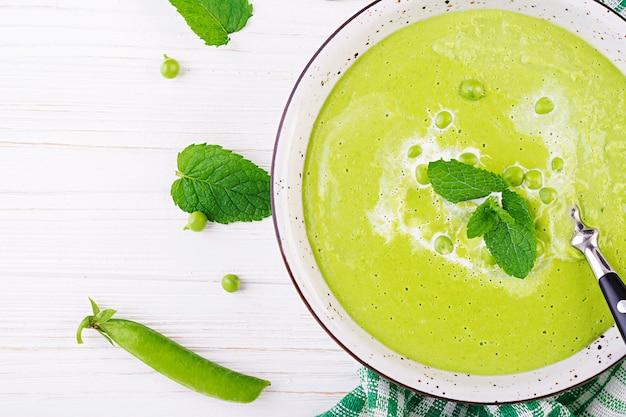 Suppe der grünen erbse in der schüssel auf holztisch, französische küche, draufsicht