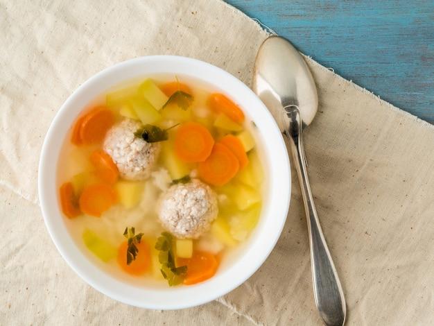 Suppe, eine tasse brühe und gemüse, fleischbällchen aus truthahn und hühnchen