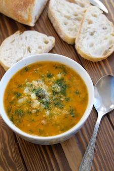 Suppe in einer platte mit scheiben brot auf einem holztisch.