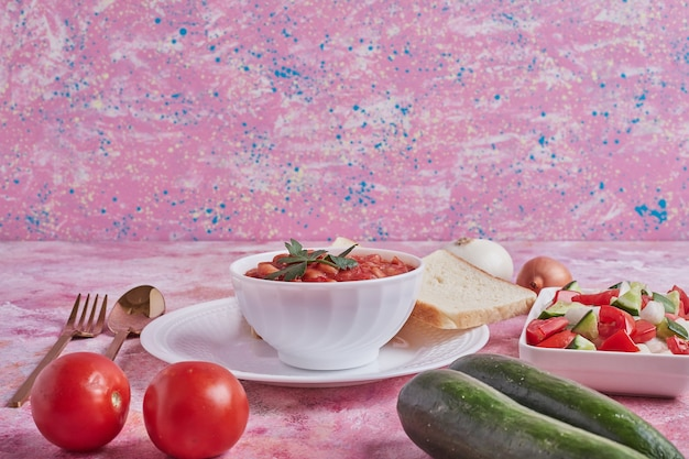 Suppe in tomatensauce mit gemüsesalat.