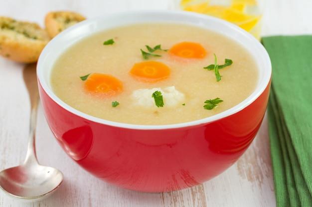 Suppe mit blumenkohl und karotten in der schüssel