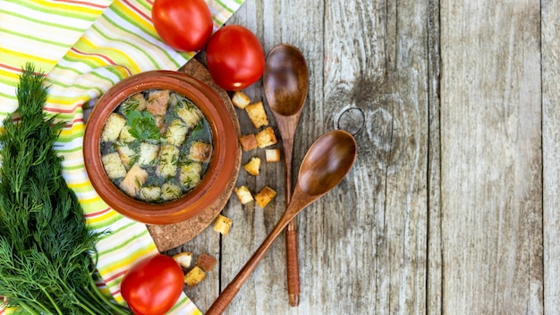 Suppe mit croutons und kräutern in einem topf