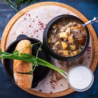 Suppe mit fleisch, pilzen und gemüse in einem topf draufsicht
