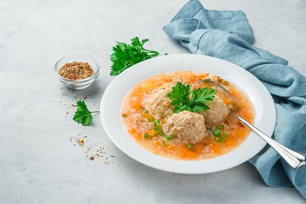 Suppe mit fleischbällchen auf grauem hintergrund. seitenansicht, platz zum kopieren. gesundes essen.