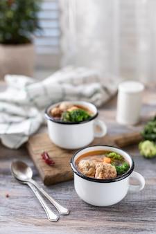 Suppe mit fleischbällchen in metallbechern auf holztisch