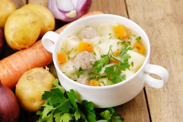 Suppe mit fleischbällchen mit gemüse beiseite