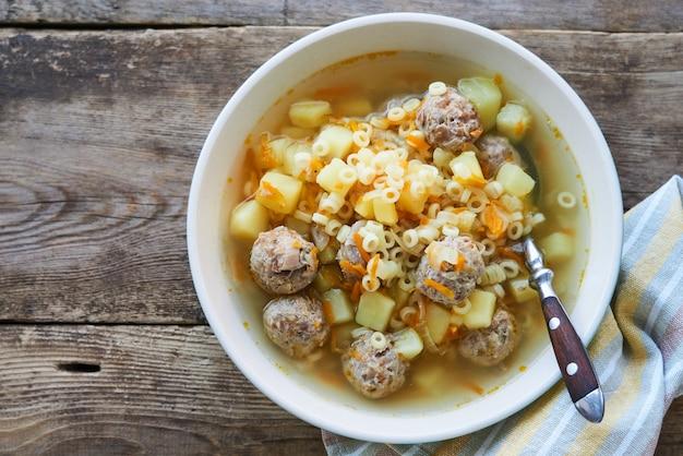 Suppe mit fleischbällchen, pasta anellini und gemüse in einer schüssel