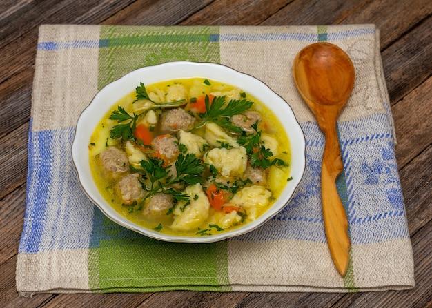 Suppe mit fleischbällchen und knödel und einem hölzernen wacholderlöffel auf einer leinenserviette hautnah