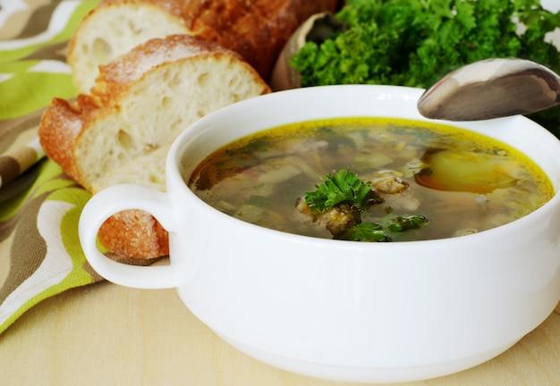 Suppe mit fleischbällchen und petersilie zum abendessen