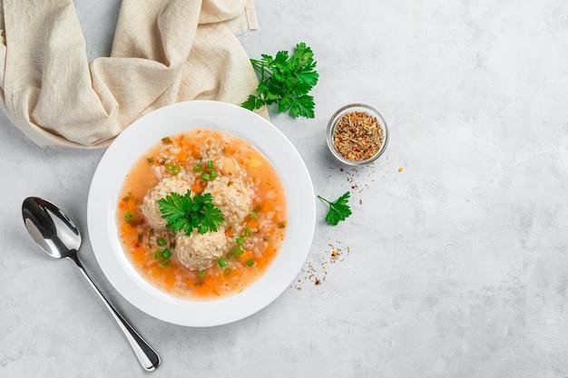 Suppe mit fleischbällchen und reis auf grauem hintergrund mit dill und gewürzen. ansicht von oben. gesundes essen.