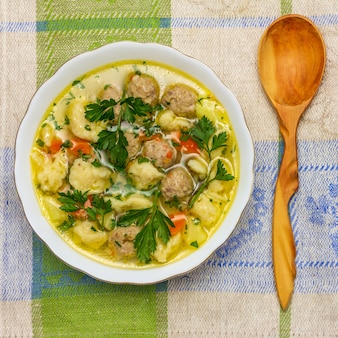 Suppe mit fleischklöschen und mehlklößen und einem hölzernen wacholderbuschlöffel auf einer draufsicht der leinenserviettennahaufnahme