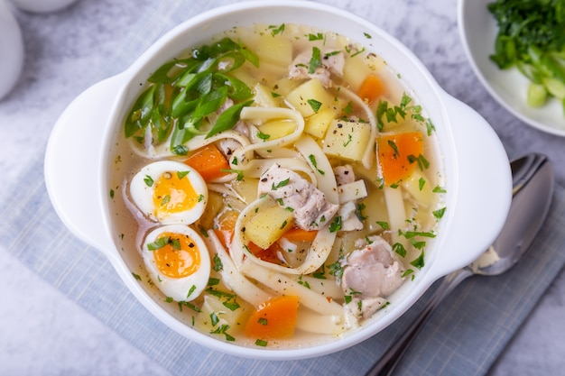 Suppe mit hühnchen, nudeln, kartoffeln, wachteleiern und karotten
