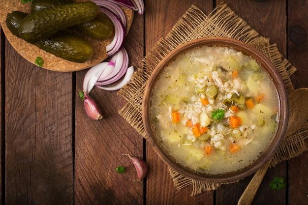 Suppe mit in essig eingelegten gurken und perlgerste - rassolnik auf einem hölzernen hintergrund. draufsicht.