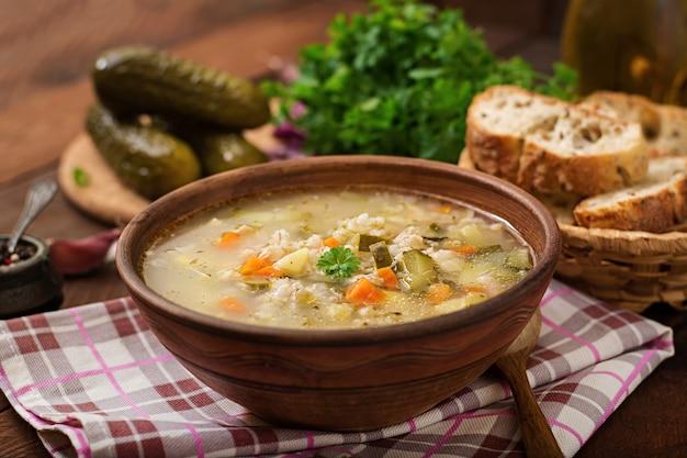 Suppe mit in essig eingelegten gurken und perlgerste - rassolnik auf einem hölzernen hintergrund.