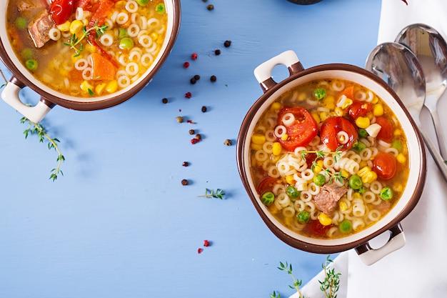 Suppe mit kleinen nudeln, gemüse und fleischstücken in einer schüssel auf einem blauen tisch. italienisches essen. draufsicht. flach liegen