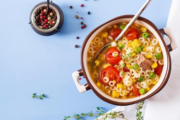 Suppe mit kleinen teigwaren, gemüse und fleischstücken in der schüssel auf blauer tabelle. italienisches essen.