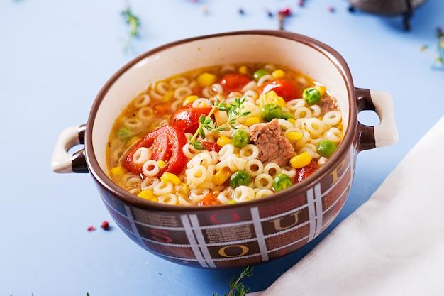 Suppe mit kleinen teigwaren, gemüse und fleischstücken in der schüssel auf blauer tabelle.