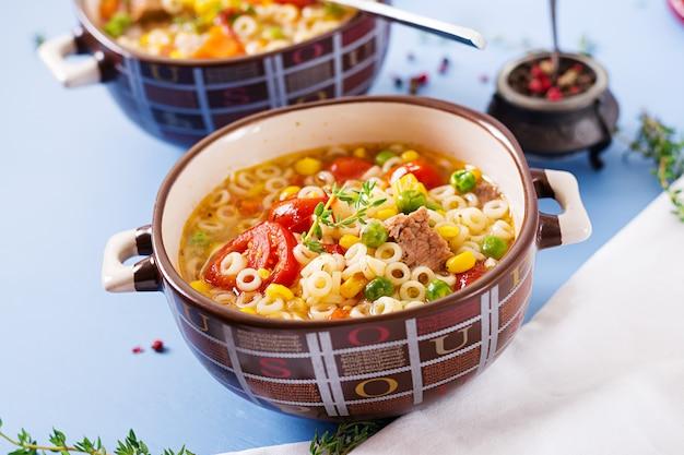Suppe mit kleinen teigwaren, gemüse und stücken fleisch in der schüssel auf blauer tabelle. italienisches essen.