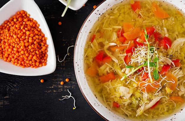 Suppe mit linsen, karotten, hühnerfleisch, paprika, sellerie in einer schüssel.