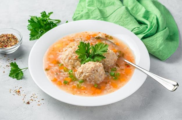 Suppe mit putenfleischbällchen und reis mit frischen kräutern. seitenansicht, nahaufnahme. gesundes essen.