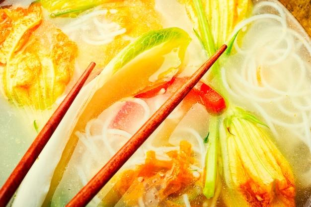 Suppe mit reisnudeln und kürbisblumen. asiatische vegane suppe. lebensmittelhintergrund