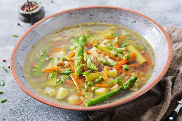 Suppe mit rindfleisch, spargel, grünen erbsen, karotten und sellerie. gesundes essen.