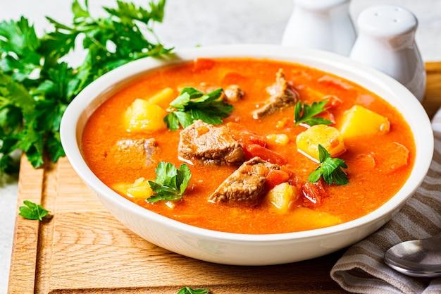 Suppe mit rindfleisch und gemüse in einem weißen teller auf einem holzbrett.