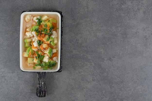 Suppe mit verschiedenen gemüsescheiben auf weißem teller. foto in hoher qualität