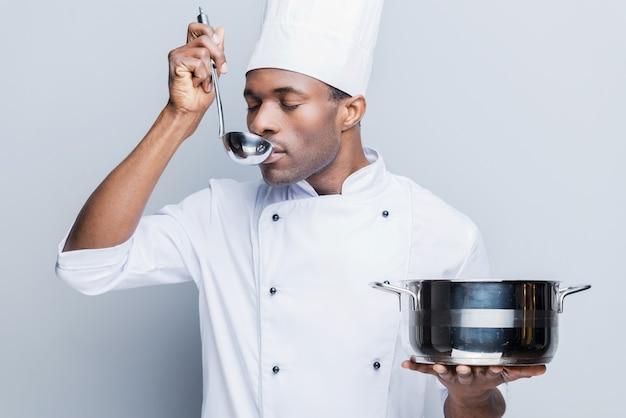 Suppe probieren. selbstbewusster junger afrikanischer koch in weißer uniform mit auflauf und schaufel