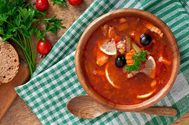 Suppe solyanka russe mit fleisch, oliven und essiggurken in der hölzernen schüssel