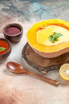 Suppe zitronenkürbissuppe auf dem brett löffel sauce gewürze