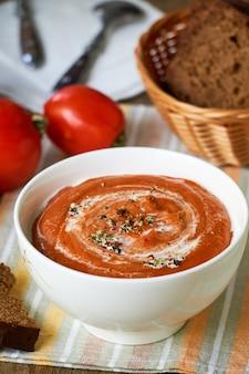 Suppenpüree mit gebackenen tomaten in einer weißen schüssel