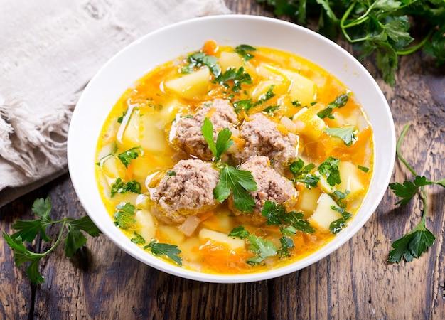 Suppenteller mit fleischbällchen auf holztisch