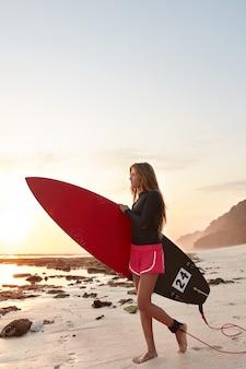 Surfboarder mit angenehmem aussehen trägt board
