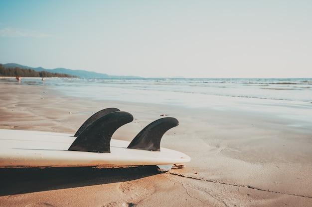 Surfbrett auf tropischem strand des sandes mit ruhigem see- und himmelhintergrund des meerblicks. sommerferienhintergrund und wassersportkonzept. vintage farbton-effekt.