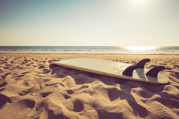 Surfbrett auf tropischem strand des sandes mit ruhigem see- und sonnenunterganghintergrund des meerblicks.