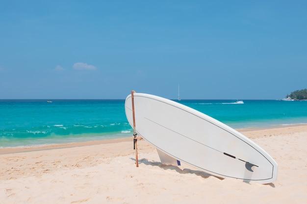 Surfbrett auf tropischem strand mit blauem meer im sommer