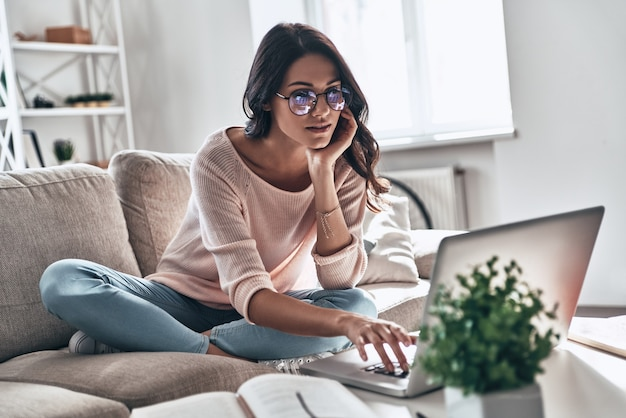 Surfen im internet. nachdenkliche junge frau in brillen mit computer beim sitzen auf dem sofa zu hause