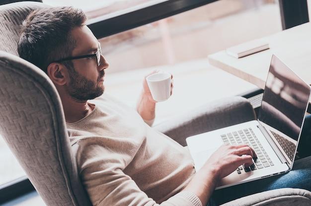 Surfen im internet vom café. seitenansicht eines gutaussehenden mannes, der seinen laptop benutzt und eine kaffeetasse hält, während er auf einem stuhl vor dem fenster sitzt